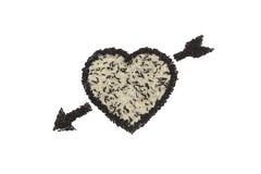 Forma y flecha del corazón de la mezcla de arroz blanco y de arroz negro en el fondo blanco Fotografía de archivo libre de regalías