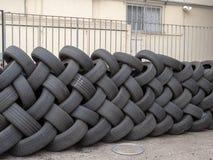 Formación de neumáticos de repuesto que se colocan entrelazados para formar la pared fotografía de archivo