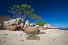 Formación de roca en la playa arenosa tropical fotografía de archivo