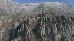 Formación de roca formada enorme y extraña en la ladera de la montaña con los arbustos y los pequeños árboles tiro Silueta del ho almacen de video