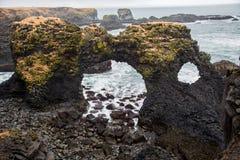 Formación de roca de lava con el agujero y el mar fotos de archivo