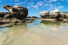 Formación de roca una piscina del océano con reflexiones en el mar en la playa de Peterborough, Victoria, Australia Foto de archivo