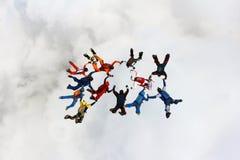 Formación que salta en caída libre sobre la nube blanca fotografía de archivo