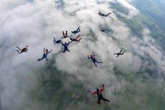 Formación que salta en caída libre sobre las nubes blancas fotos de archivo