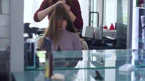 Formaci?n de filamentos del pelo con las manos y el peine para dise?ar del pelo El peluquero hace un peinado festivo de moda en l almacen de metraje de vídeo