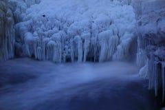 Formaciones de hielo y un pequeño pájaro por una cascada congelada Imagenes de archivo