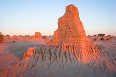 Formaciones de la erosión en el rosa del resplandor de la lana de borra del lago en la puesta del sol Foto de archivo libre de regalías