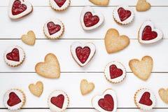 Formad hjärta och mördegskakakakor med driftstoppgåvasammansättning för valentindag på tappningträbakgrund Arkivfoton