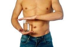 Formad och sund man som rymmer ett mineralvattenexponeringsglas Royaltyfri Foto