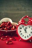 Formad röd förälskelseklocka för valentin hjärta med choklader Arkivfoton