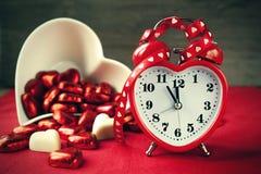Formad röd förälskelseklocka för valentin hjärta med choklader Royaltyfri Bild