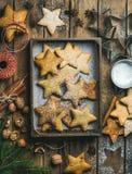 Formade kakor för pepparkaka skyler över brister stjärnan i trämagasin med bakning royaltyfria bilder
