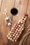 Formade korkar för vinflaska, exponeringsglas av rött vin och korkskruv Arkivfoton