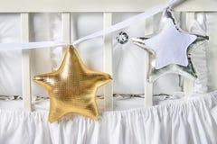 Formade kuddar för silver och för guld behandla som ett barn stjärnan på ett vitt kåtan Fotografering för Bildbyråer