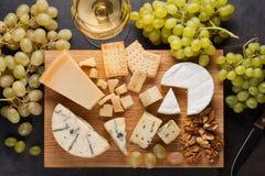 Formaggi assortiti con l'uva bianca, le noci, i cracker ed il vino bianco su un bordo di legno Alimento per una data romantica su fotografia stock libera da diritti