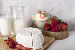 Formaggi assortiti sul bordo di legno Camembert, formaggio con muffa blu, gouda, formaggio a pasta dura, fragole fotografie stock libere da diritti