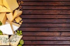 Formaggi differenti sulla tavola di legno con spazio vuoto Cheddar, parmigiano, emmental, formaggio blu Vista superiore, spazio d Fotografia Stock Libera da Diritti
