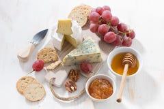 formaggi, frutta e spuntini modellati su un bordo di legno bianco Immagine Stock