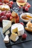 Formaggi, vino ed uva modellati su una lavagna Immagine Stock