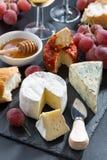 Formaggi, vino ed uva modellati su una lavagna, verticale Fotografia Stock Libera da Diritti