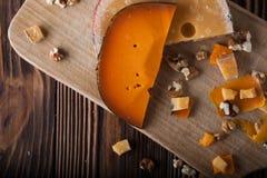 Formaggio arancio su un bordo di legno con i dadi Fotografia Stock