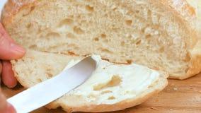 Formaggio cremoso di diffusione sul pane della brioche video d archivio