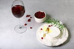 Formaggio del camembert con un vetro di vino rosso, mirtillo rosso di frutti, colpo da sopra su fondo leggero con lo spazio della immagine stock libera da diritti