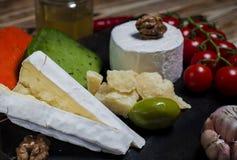 Formaggio della miscela su fondo scuro sul bordo di legno con l'uva, il miele, i dadi, i pomodori ed il basilico Vista superiore immagine stock