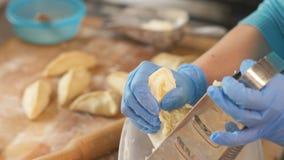 Formaggio dello sfregamento del panettiere della mano sulla grattugia per la torta nella fine della cucina del forno su immagini stock