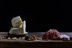 Formaggio di Bree del francese, dadi e bugia secca della carne su un tagliere o Fotografie Stock Libere da Diritti