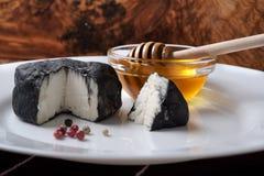 Formaggio di capra delizioso coperto di cenere nera e di miele Fotografia Stock
