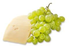 Formaggio ed uva su una priorità bassa bianca Immagine Stock