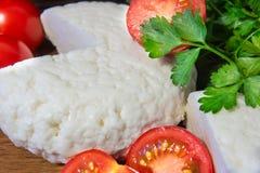 Formaggio fresco con gusto ed aroma eccellenti Formaggio sul tagliere di legno con i pomodori e le erbe fresche immagine stock