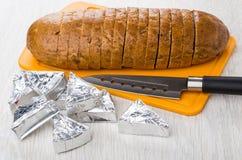 Formaggio fuso in foglio di alluminio, pane sul tagliere, coltello Immagine Stock Libera da Diritti