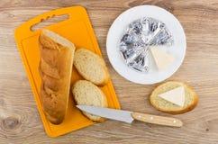 Formaggio fuso in piatto, pane, panino con formaggio e coltello Immagini Stock