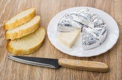 Formaggio fuso in stagnola in piatto, pane e coltello da cucina Fotografie Stock Libere da Diritti