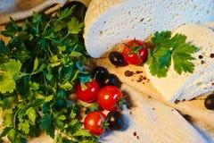 formaggio georgiano casalingo su un bordo di legno, pomodori ciliegia, noci, uva, spezie di Imeretian immagini stock libere da diritti