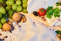 formaggio georgiano casalingo su un bordo di legno, pomodori ciliegia, noci, uva, spezie di Imeretian immagine stock
