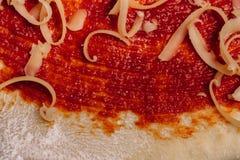 Formaggio grattugiato per la fine della pizza su sulla pasta rivestita del ketchup fotografia stock libera da diritti