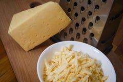 Formaggio olandese grattato in un piatto su un bordo Fotografia Stock