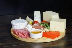 Formaggio platte con differenti formaggi, carni sul bordo di legno Fotografia Stock