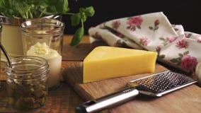 Formaggio sul tagliere e sulla grattugia con basilico fresco sul tavolo da cucina di legno video d archivio