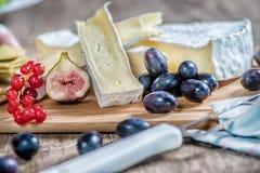 Formaggio sulla tavola Brie affettato su una tavola e su uno SL di legno Fotografia Stock