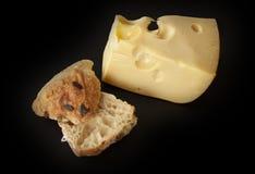Formaggio svizzero dell'emmental e un panino al forno domestico su fondo nero immagini stock