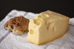 Formaggio svizzero dell'emmental e un panino al forno domestico sul fondo bianco del panno immagini stock