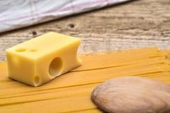 Formaggio svizzero e pasta su un fondo di legno Fotografia Stock