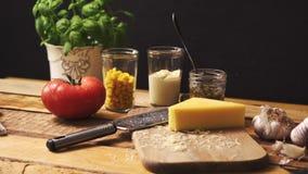 Formaggio tagliuzzato con basilico fresco e pomodoro succoso sul tavolo da cucina di legno stock footage