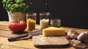 Formaggio tagliuzzato con basilico fresco e pomodoro succoso sul tavolo da cucina di legno archivi video