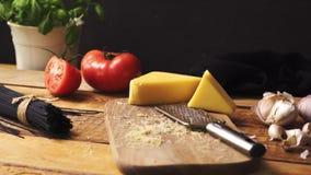 Formaggio tagliuzzato con basilico fresco e spaghetti italiani sul tavolo da cucina di legno archivi video