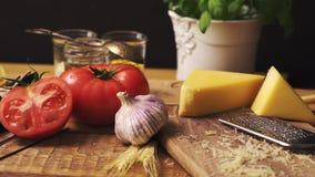 Formaggio tagliuzzato con basilico fresco e spaghetti italiani sul tavolo da cucina di legno video d archivio
